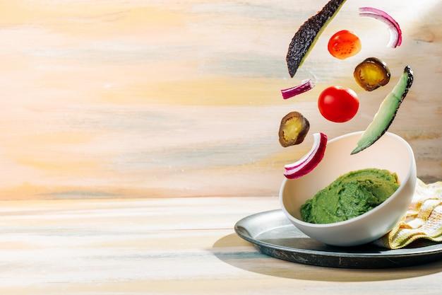 Domowa miska guacamole z pływającymi wokół niej składnikami. vintage drewniany stół. zdrowe jedzenie