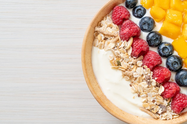 Domowa miska jogurtowa z malinami, jagodami, mango i muesli - styl zdrowej żywności