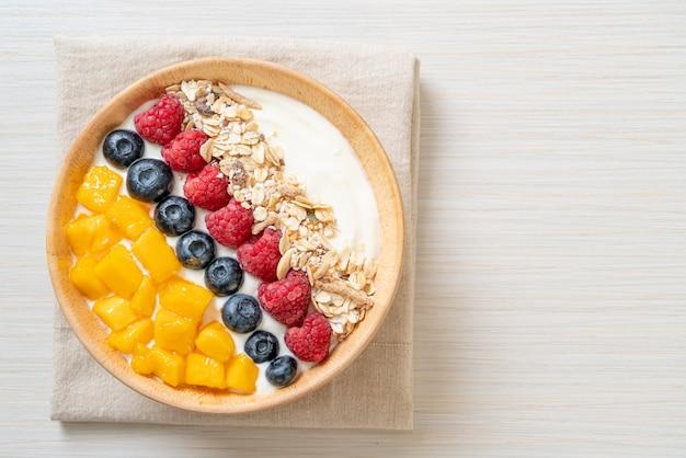 Domowa miska na jogurt z malinami, jagodami, mango i granolą - zdrowy styl jedzenia