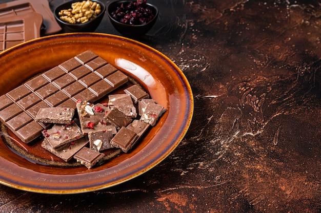 Domowa mleczna czekolada z orzechami laskowymi, orzeszkami ziemnymi, żurawiną i liofilizowanymi malinami na rustykalnym talerzu. ciemne tło. widok z góry. skopiuj miejsce.