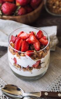 Domowa muesli z kawałkami czekolady, truskawkami i jogurtem w szklance na rustykalnym drewnianym tle. zdrowe śniadanie.