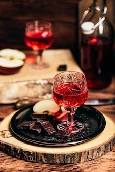 Domowa nalewka z czerwonej porzeczki i czekolady z pokrojonym jabłkiem na metalowej tacy