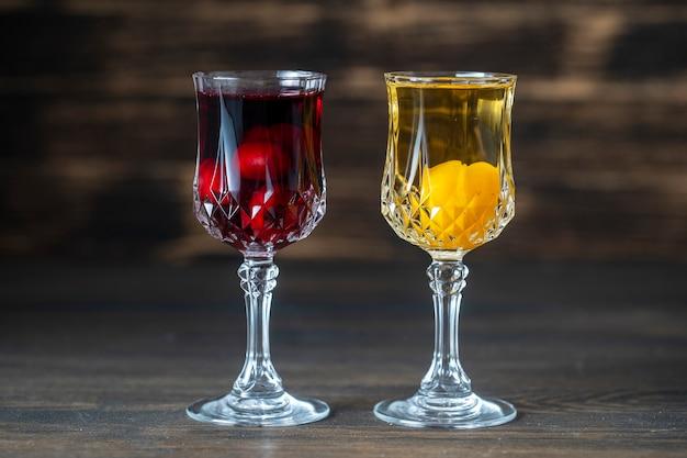 Domowa nalewka z czerwonej wiśni i żółtej śliwki wiśniowej w kieliszkach do wina kryształowego na podłoże drewniane
