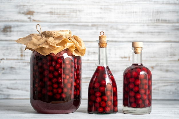 Domowa nalewka z czerwonej wiśni. koncepcja napojów alkoholowych jagód. domowe czerwone wino z dojrzałych wiśni w szklanych butelkach i słoikach