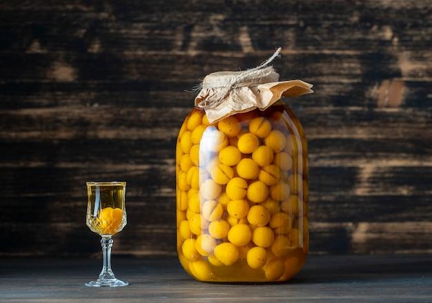 Domowa nalewka z żółtej śliwki wiśniowej w szklanym słoju i kieliszek do wina na drewnianym tle, ukraina, z bliska. koncepcja napojów alkoholowych jagodowych