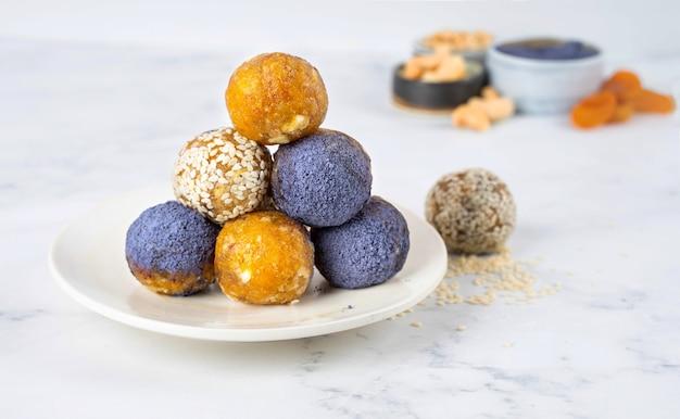 Domowa niebieska herbata matcha w proszku energetyczne kulki w ceramicznym talerzu zdrowe słodycze z orzechów, suszonych moreli, sezamu.