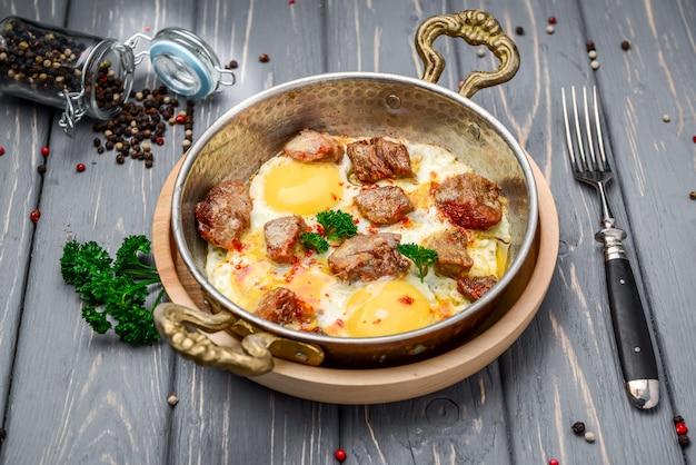 Domowa obfita śniadaniowa patelnia z jajkami i boczkiem