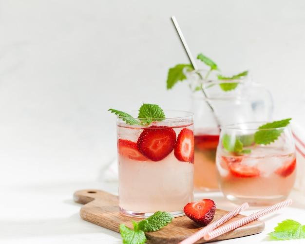 Domowa orzeźwiająca lemoniada truskawkowa w szklankach i dzbanku ze świeżymi truskawkami i listkami mięty
