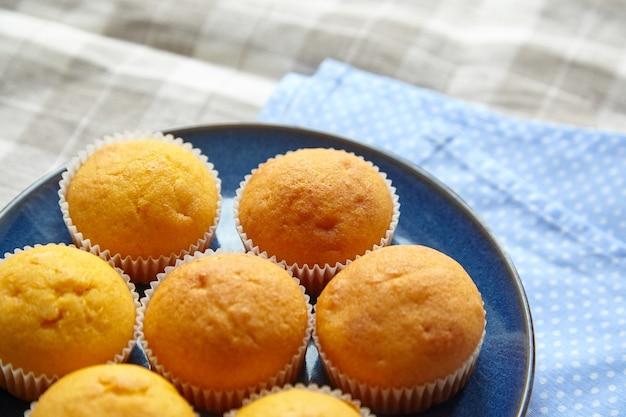 Domowa piekarnia. babeczki dyniowe na niebieskim talerzu na stole z obrusem. żywność na bazie roślin