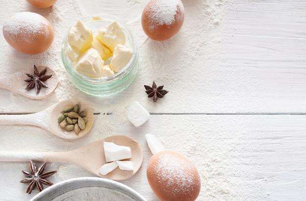 Domowa piekarnia. składniki do pieczenia na drewnianym stole kuchennym - masło, jajka, mąka i przyprawy
