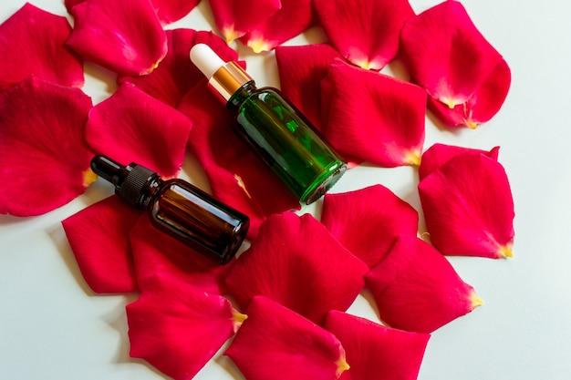 Domowa pielęgnacja skóry naturalna woda różana, produkt z olejkami eterycznymi. czerwone płatki róż i szklana butelka kosmetyczna z zakraplaczem do serum nawilżającego, toniku do twarzy, oczyszczania, demakijażu lub leczenia trądziku.