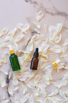 Domowa pielęgnacja skóry naturalna woda różana, produkt z olejkami eterycznymi. płatki piwonii i szklane butelki kosmetyczne z zakraplaczem do serum nawilżającego, toniku do twarzy, oczyszczania, demakijażu lub leczenia trądziku.