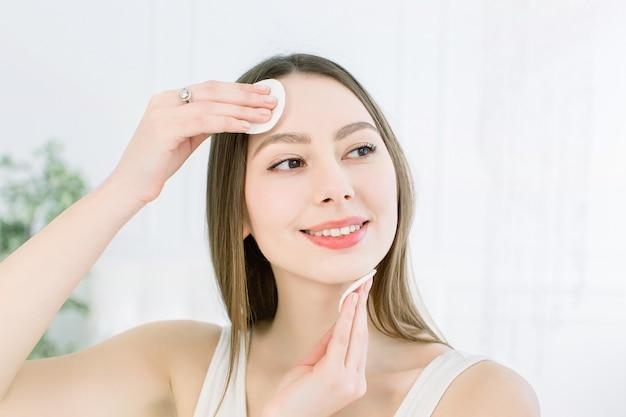 Domowa pielęgnacja twarzy. idealna świeża skóra. piękna twarz młodej kobiety usuwanie makijażu. ręka kobiety z wacikiem. czyść skórę bawełną. koncepcja piękna, pielęgnacja skóry i problemy skórne