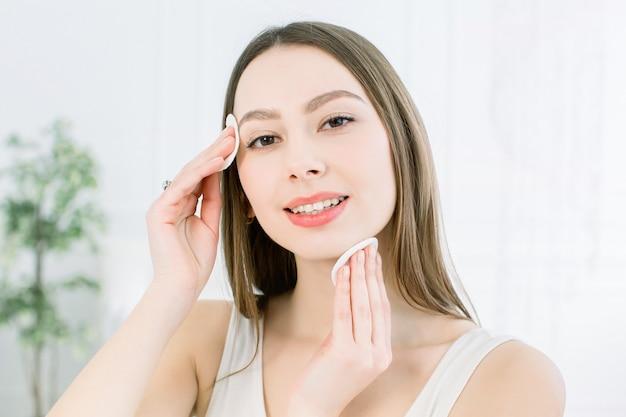 Domowa pielęgnacja twarzy. idealna świeża skóra. piękna twarz młodej kobiety usuwanie makijażu. ręka kobiety z wacikiem. czyść skórę bawełną. koncepcja pielęgnacji skóry