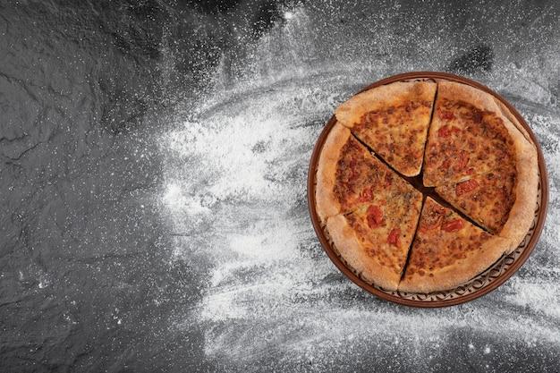 Domowa pizza w plasterkach na brązowym talerzu na czarnej powierzchni