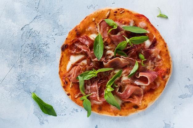 Domowa pizza z jamonem, mozzarellą i świeżymi liśćmi bazylii