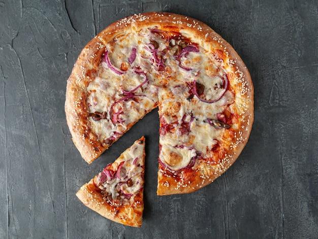 Domowa pizza z kiełbaskami myśliwskimi, marynowaną czerwoną cebulą, pieczarkami, serem mozzarella i sosem pomidorowym. kawałek jest odcięty od pizzy. widok z góry. na szarym tle betonu. odosobniony.