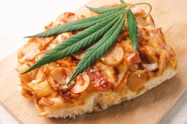 Domowa pizza z liściem marihuany lub konopi na drewnianej tacy.