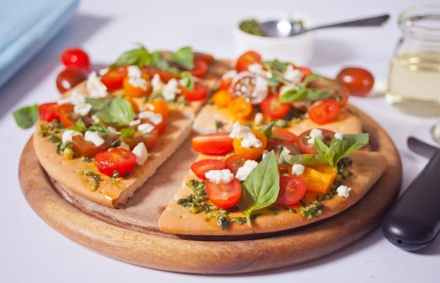 Domowa pizza z pomidorami koktajlowymi, świeżą zieloną bazylią i serem feta. domowe jedzenie. pomysł na smaczny i obfity posiłek. ścieśniać.