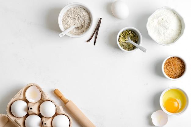 Domowa produkcja świeżego zdrowego pieczywa z innych ciast z naturalnych składników na jasnoszarym stole.