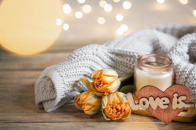 Domowa romantyczna martwa miłość jest na walentynki z kwiatami i elementami dekoracyjnymi na rozmytym tle z bokeh.