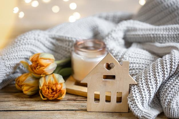 Domowa romantyczna martwa natura ze świecą, dekoracją, kwiatami i dzianiną na rozmytym tle z bokeh.