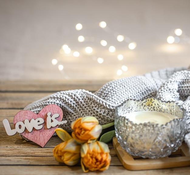 Domowa romantyczna martwa natura ze świecą, dekoracją, świeżymi kwiatami i dzianiną