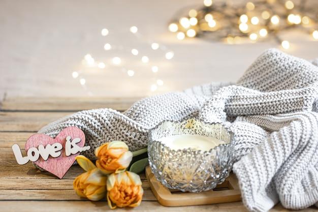 Domowa romantyczna martwa natura ze świecą, dekoracją, świeżymi kwiatami i elementem z dzianiny na rozmytym tle z bokeh.