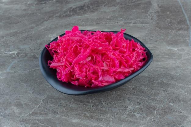 Domowa różowa kiszona kapusta w czarnej misce