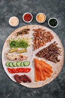 Domowa shawarma, burrito, bułka z kurczakiem i łososiem z warzywami i sosem. widok z góry na składniki z czystą przestrzenią.