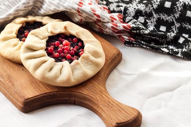 Domowa słodka galette z czarnymi jagodami i borówkami na drewnianej desce
