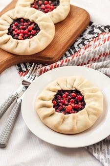 Domowa słodka galette z czarnymi jagodami i borówkami na talerzu