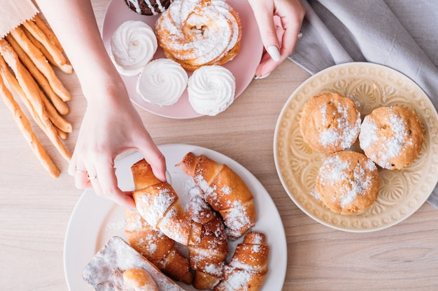 Domowa słodka piekarnia. asortyment deserów na stole. kobieta biorąc rogalika z talerza świeżych wypieków.