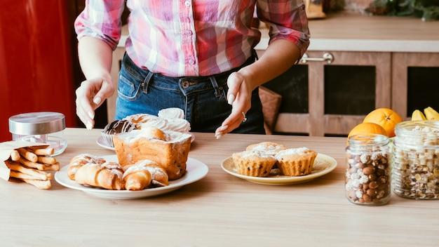 Domowa słodka piekarnia. stylista żywności. kobieta układa talerze ze świeżymi wypiekami i słoikami z orzechami na stole.