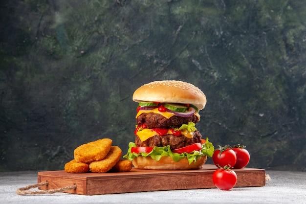 Domowa smaczna kanapka i bryłki kurczaka z pomidorami na drewnianej desce do krojenia na zamazanej powierzchni z wolną przestrzenią