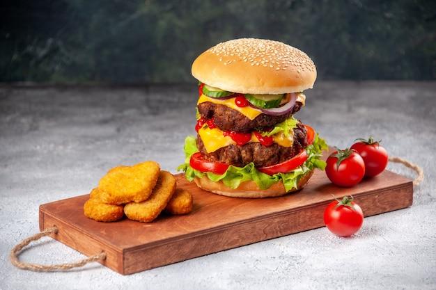 Domowa smaczna kanapka i bryłki kurczaka z pomidorami na drewnianej desce do krojenia na zamazanej powierzchni