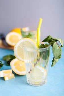 Domowa świeża woda detoksykująca z cytrynami na szarym tle i siedząca na niebieskim biurku vintage