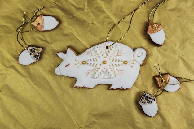 Domowa świnia z piernika pokryta białym lukrem i płatkami śniegu na złotym tle