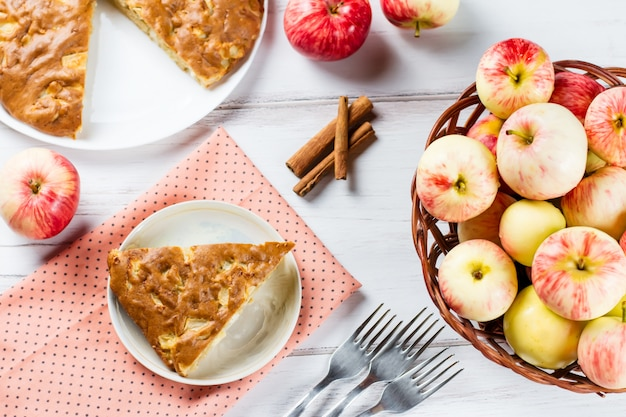 Domowa szarlotka z cynamonem i świeżymi dojrzałymi jabłkami w tle