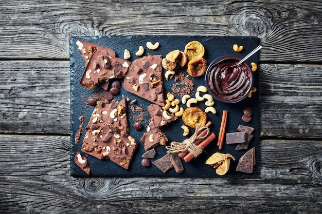 Domowa tabliczka czekolady z suszonymi figami i nadzieniem z orzechów nerkowca na czarnej kamiennej tacy ze składnikami, widok poziomy z góry, flatlay