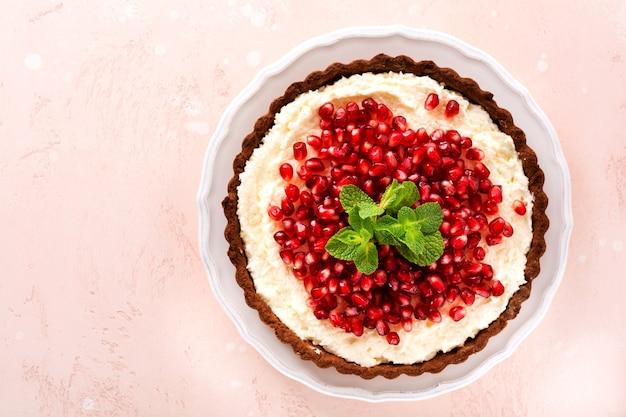 Domowa tarta czekoladowa deserowa z kremem kokosowym i granatem i miętą na różowym tle stołu. widok z góry