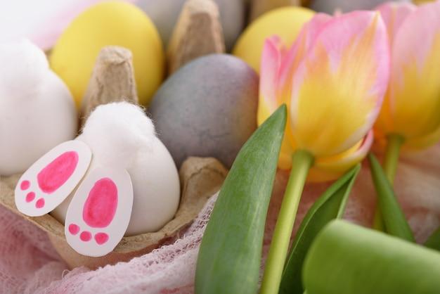 Domowa wielkanocna kompozycja żółtych i niebieskich jaj, różowych tulipanów i białych zajączków wielkanocnych, koncepcja wesołych świąt