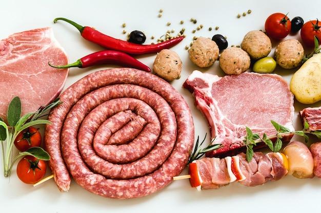 Domowa włoska kiełbasa z innymi mięsami, gotowa do gotowania na grillu. przepis śródziemnomorski