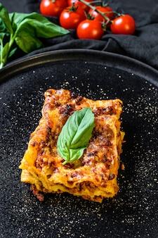Domowa włoska lasagne z sosem pomidorowym i wołowiną. czarne tło. widok z góry