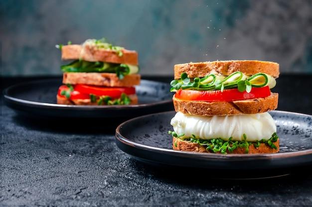 Domowa zdrowa kanapka z pełnoziarnistym chlebem, jajkiem w koszulce, ogórkiem, pomidorami i mikropłatkami sałatka z rukwi wodnej