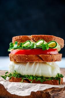Domowa zdrowa kanapka z pełnoziarnistym chlebem, jajkiem w koszulce, ogórkiem, pomidorami i sałatką z rukiewu ziołowego na desce.