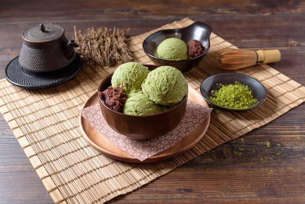 Domową zieloną herbatę lub lody matcha w drewnianej misce i nałóż bambusową matę