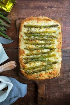Domowa zielona pizza ze szparagami z ziołami i mozzarellą