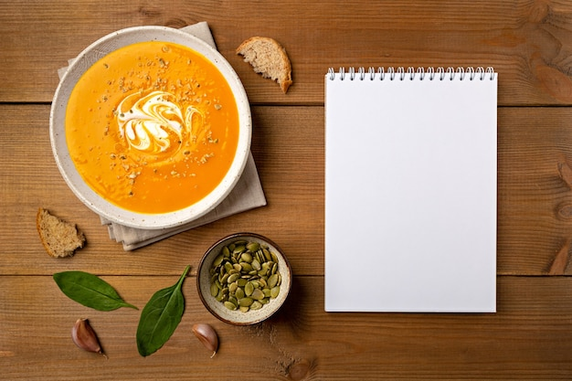 Domowa zupa dyniowa w białej misce z notatnikiem płasko leżała na brązowym drewnianym tle z miejscem na kopię.