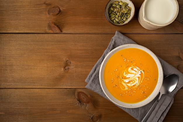 Domowa zupa dyniowa w białym talerzu na szarej serwetce płaskiej leżała na brązowym drewnianym tle z miejscem na kopię.